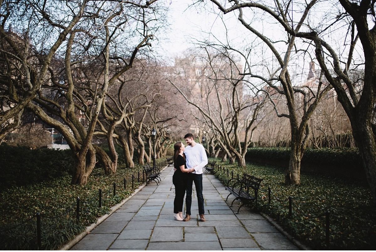 Engaged couple on treelined walk way during New York City engagement session.