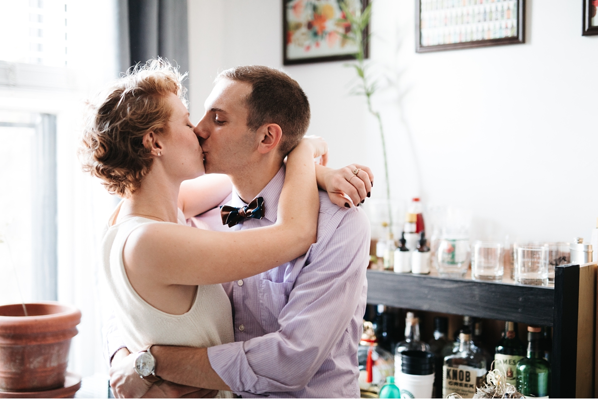 Kissing couple near window during in home engagement session