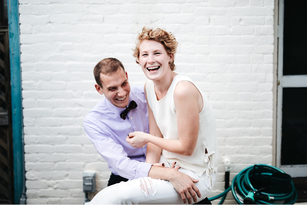 Couple laughing in Boston apartment during engagement session-2