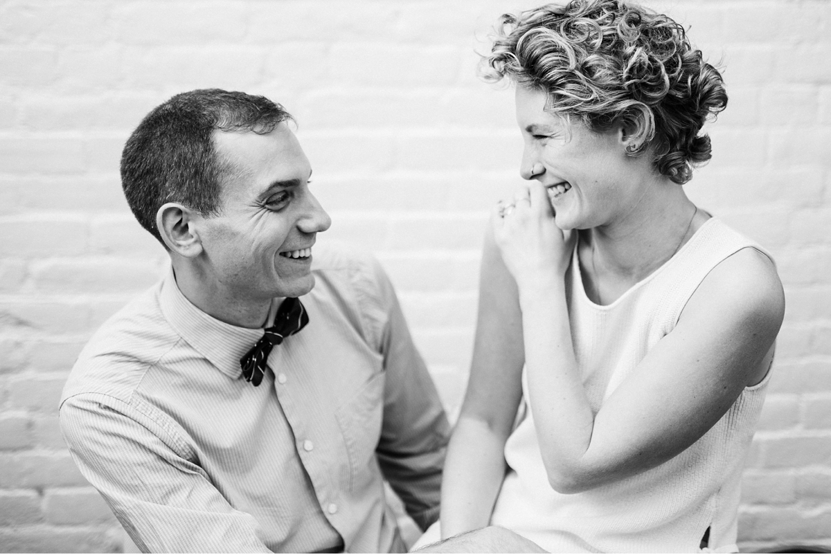 Couple laughing in Boston apartment during engagement session-3
