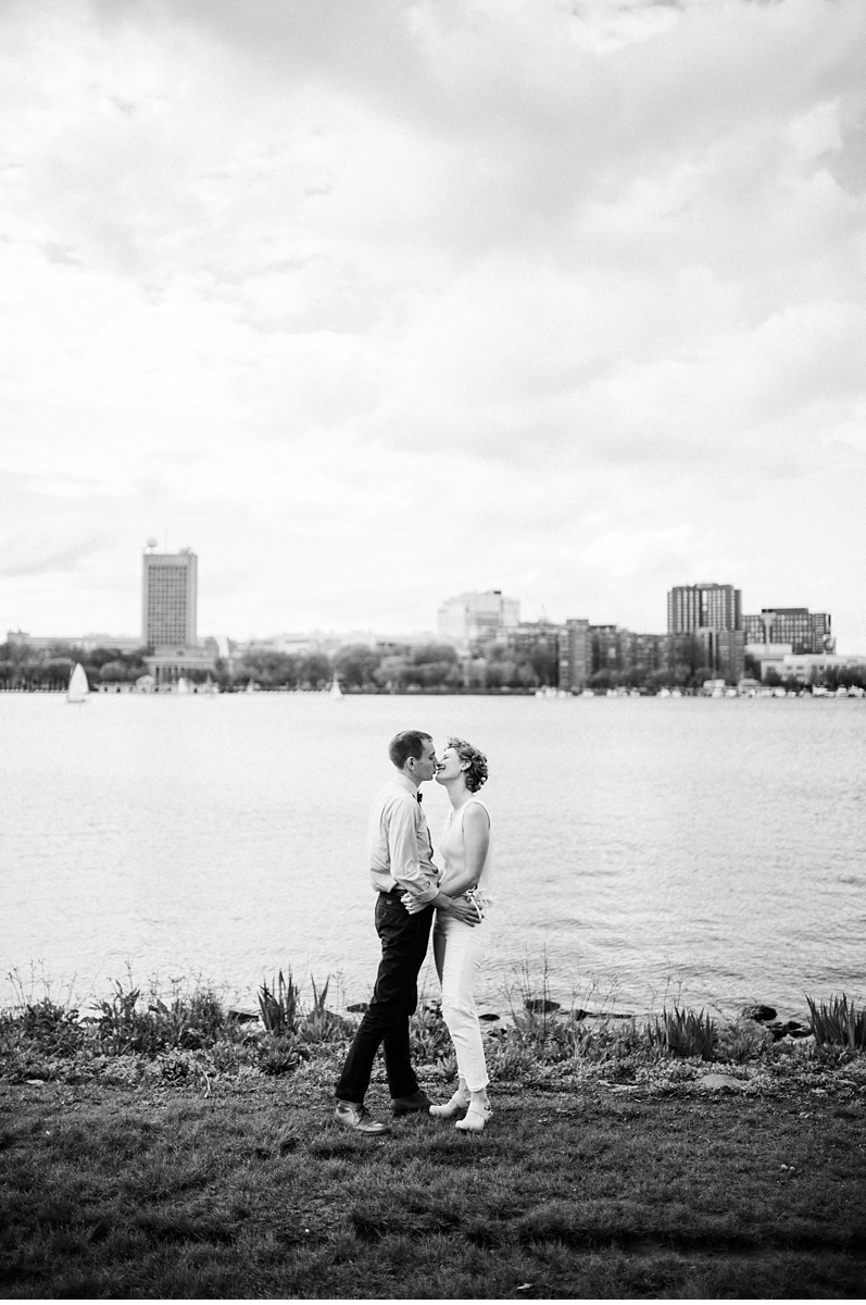 Couple kissing on riverbank in Boston MA