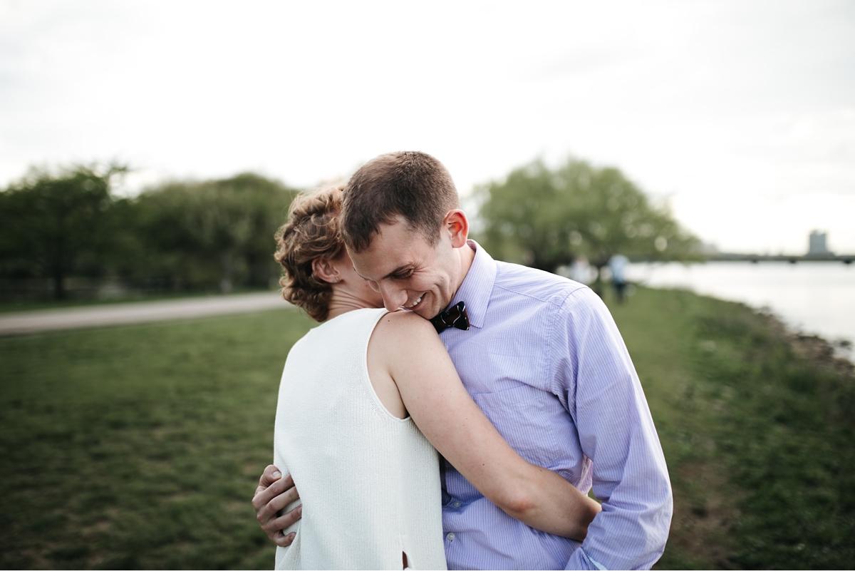 Hugging couple in riverside park, Boston engagement session