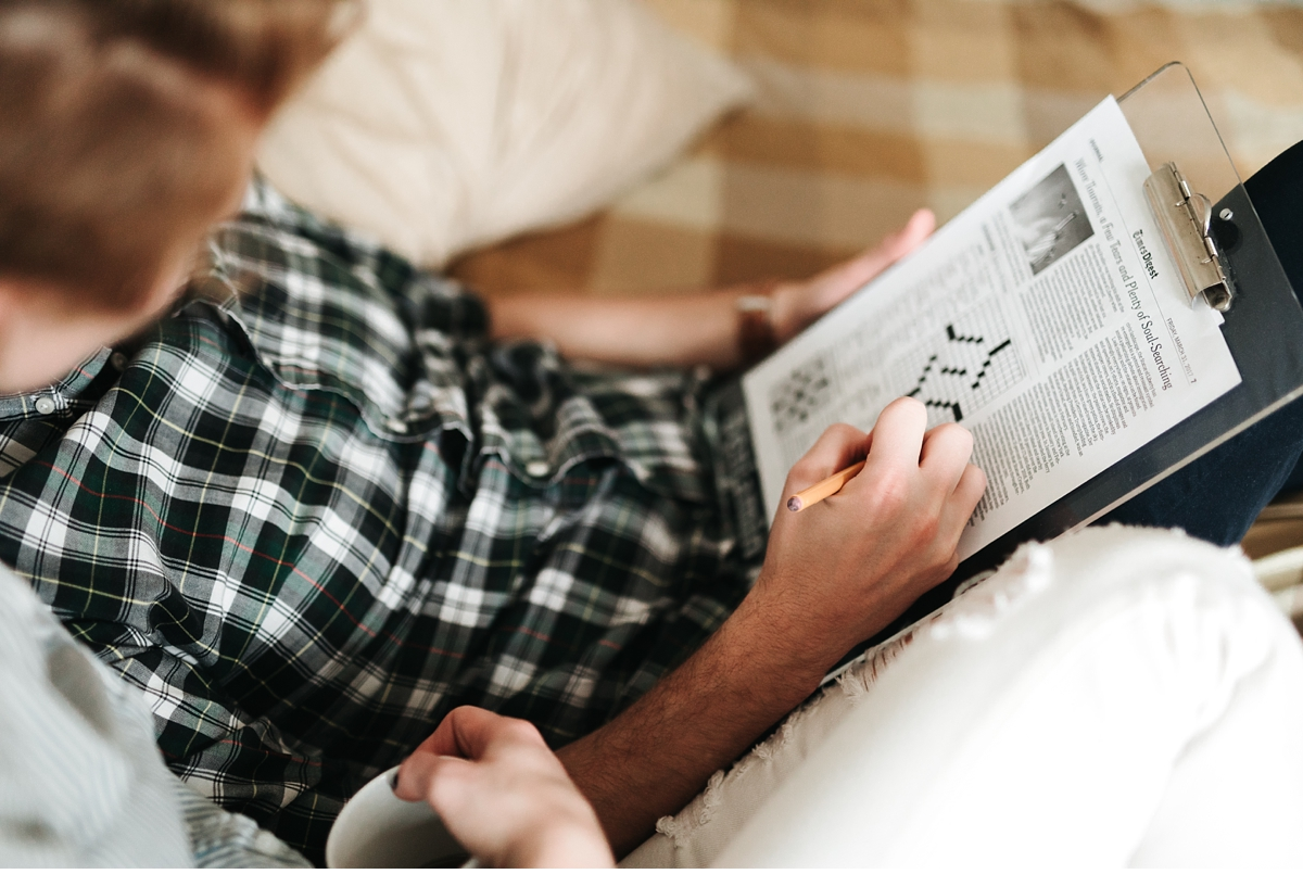 guy doing crossword puzzle in bed with fiancè