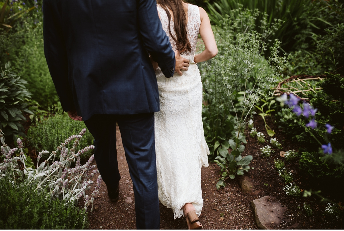 Bride and groom walking on garden path