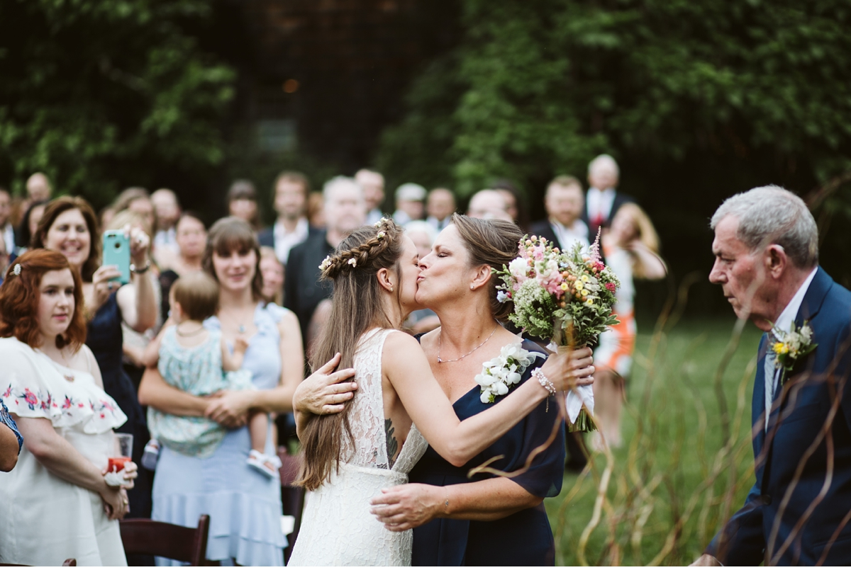 Bride kissing mom at end of isle during outdoor ceremony