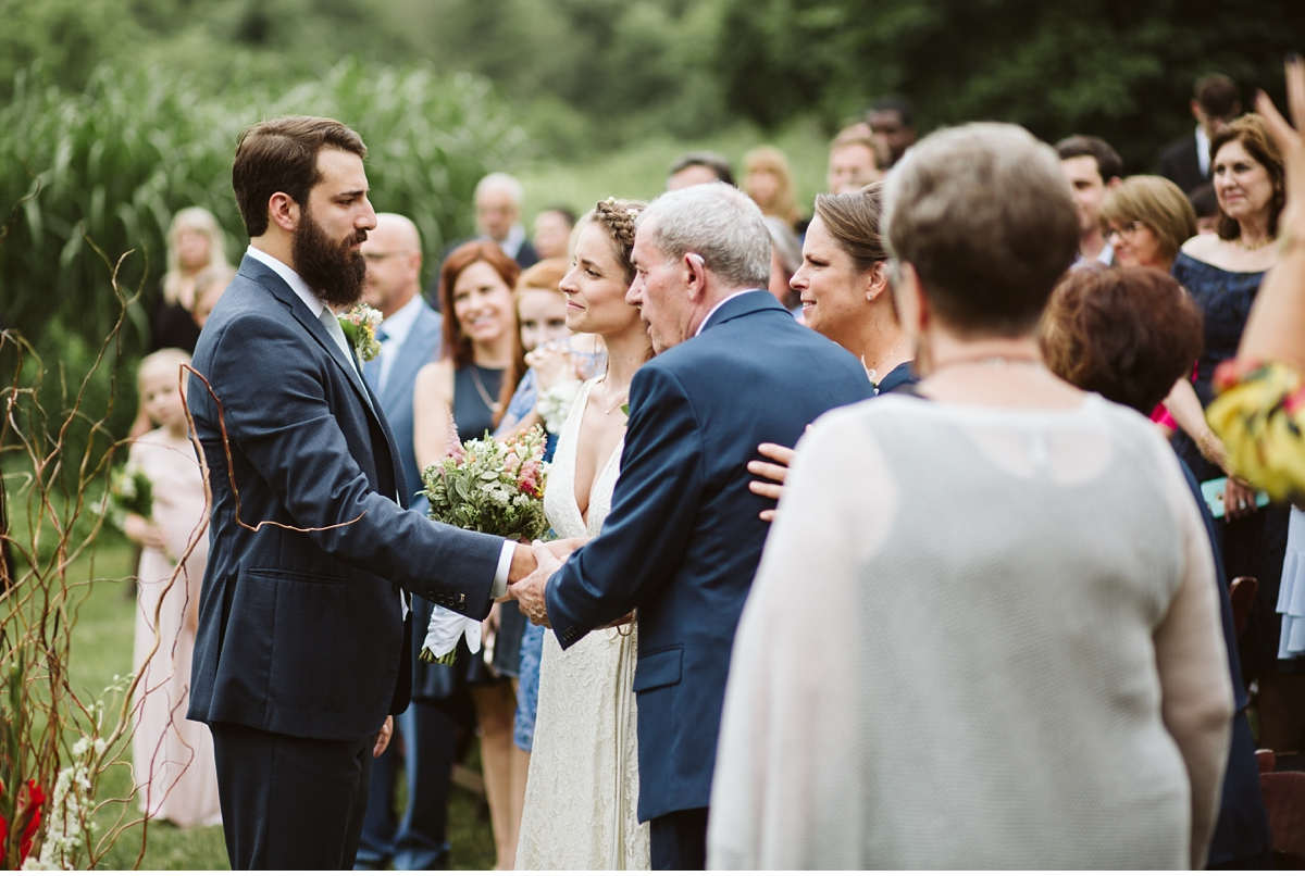 Groom shaking grandfathers hand at top of isle