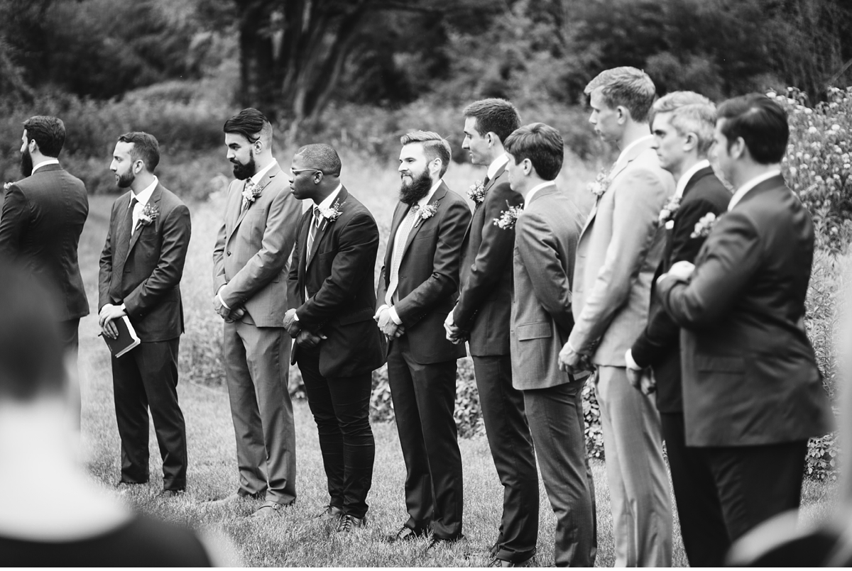 Groomsman during outdoor ceremony in black and white