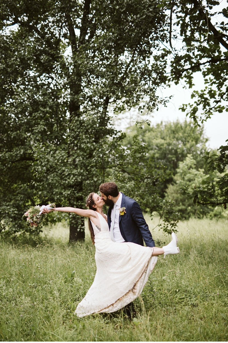 Carefree portrait of bride and groom kissing in grass