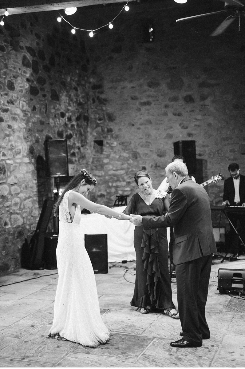 Bride dancing with family in stone barn
