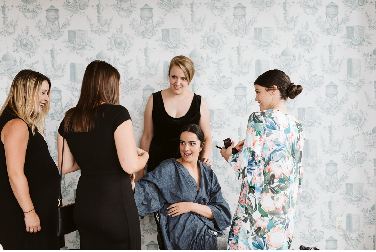 bride surrounded by friends in blue wallpaper room