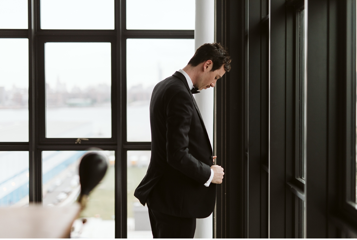 Groom buttoning his jacket in front of large window at the Wythe Hotel