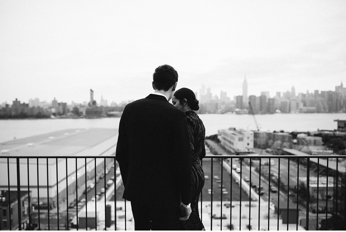 Black and white groom and bride on balcony with Manhattan skyline in background