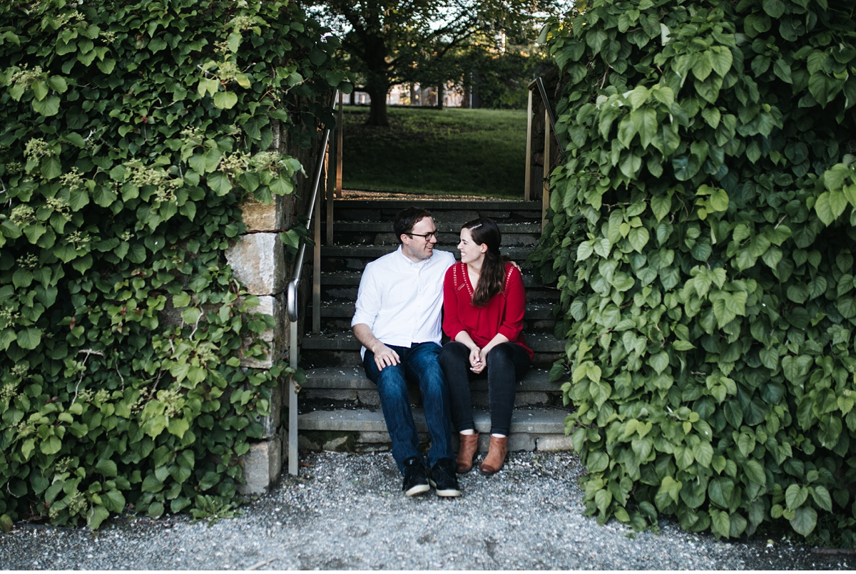 Couple sitting on stairway in between ivy covered walls.