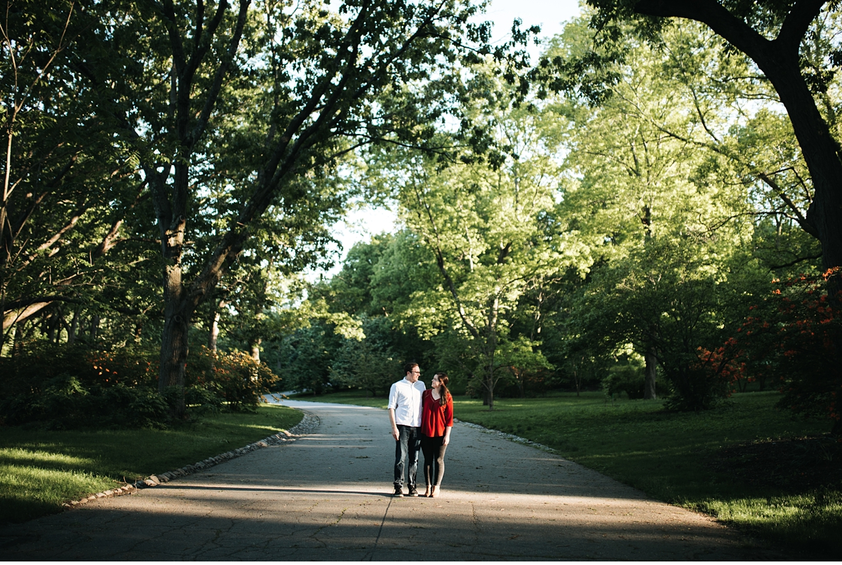 couple in the middle of a wide tree lined path in late afternoon