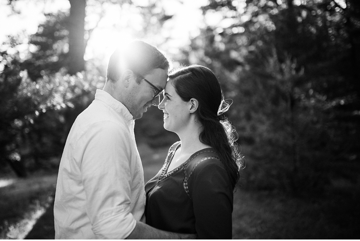 couple smiling at each other in black and white with sunflare