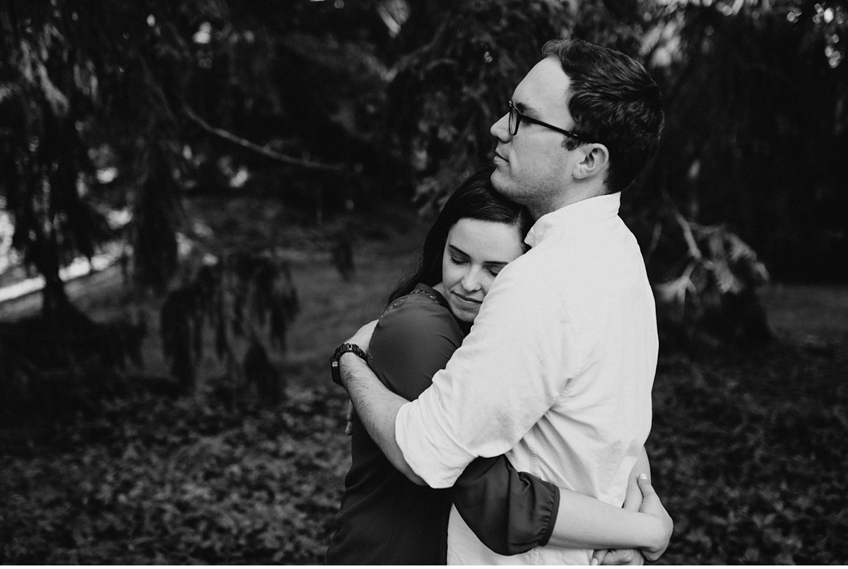 couple hugging surrounded by pine trees in the Arnold Arboretum in black and white