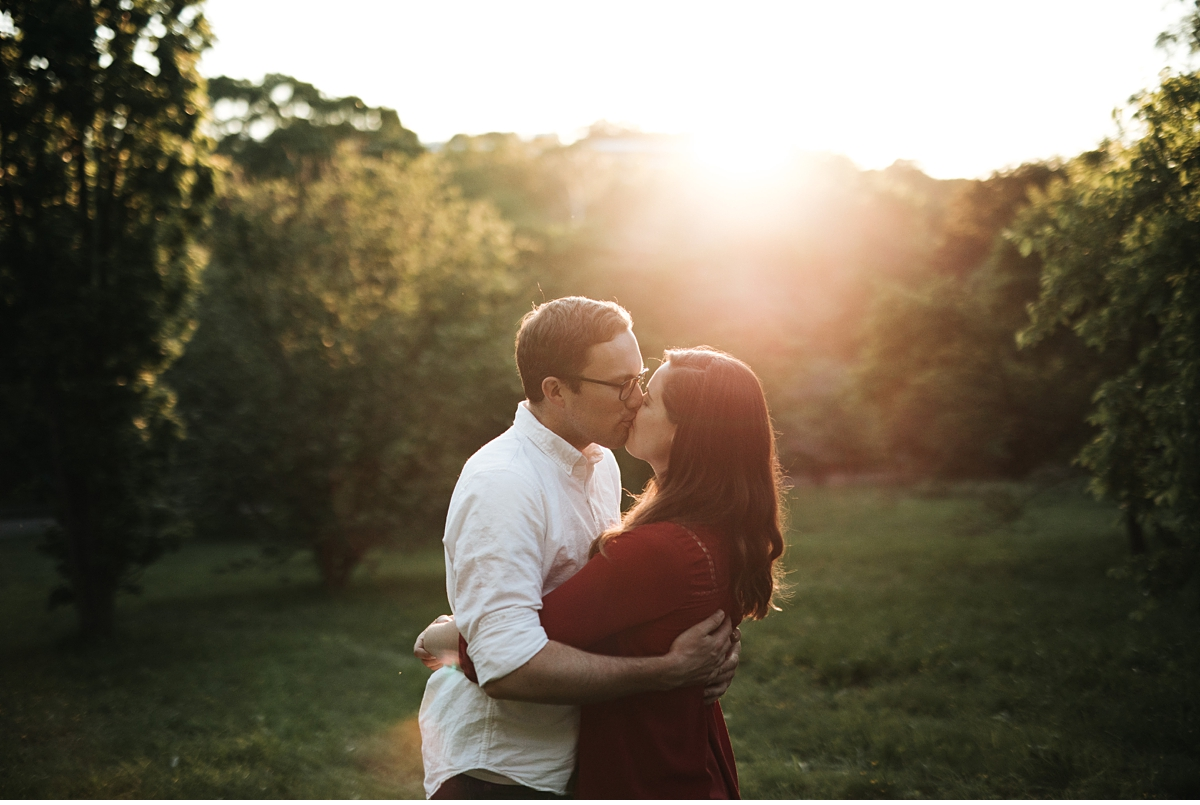 Couple kissing with sun flare during engagement session in Boston