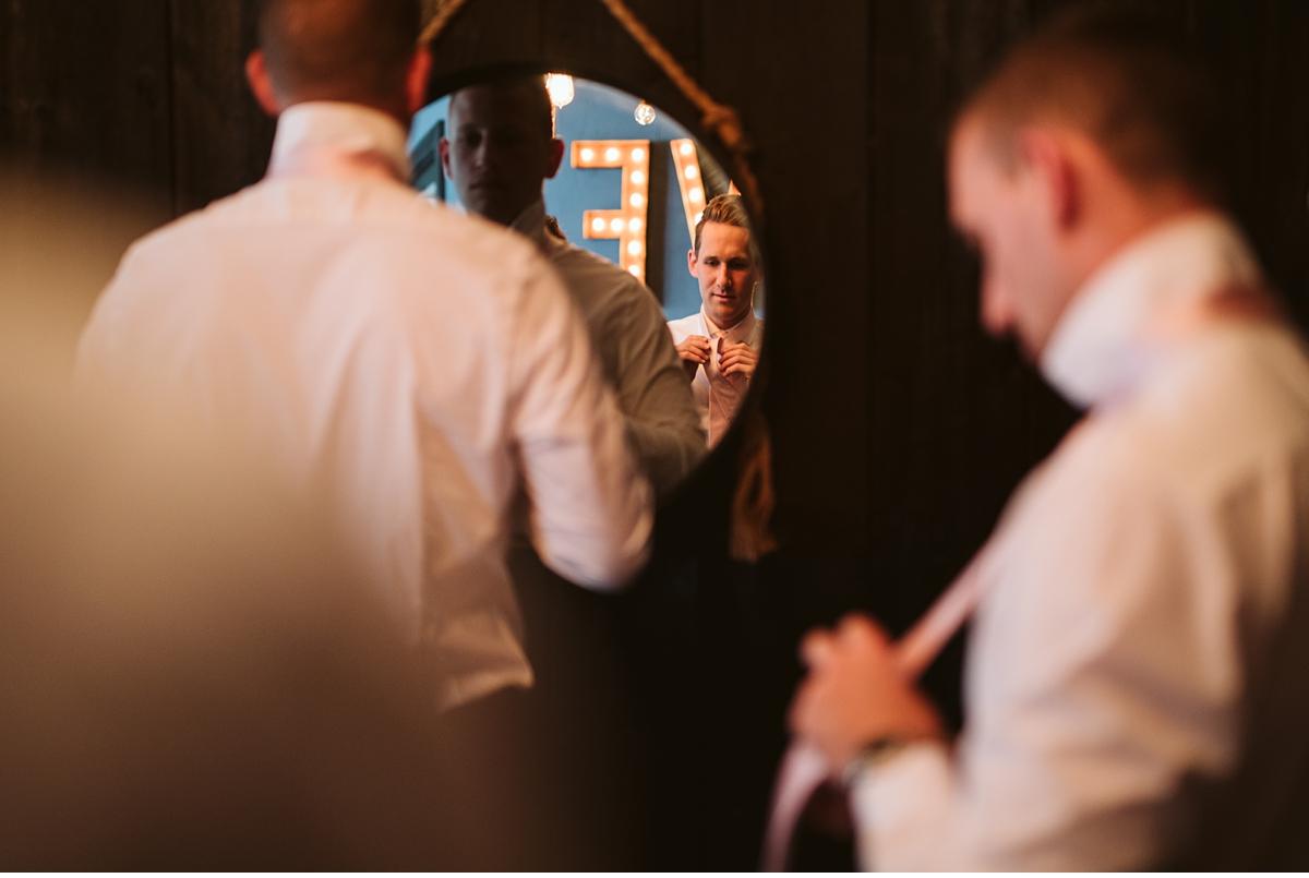 man tying tie in front of mirror