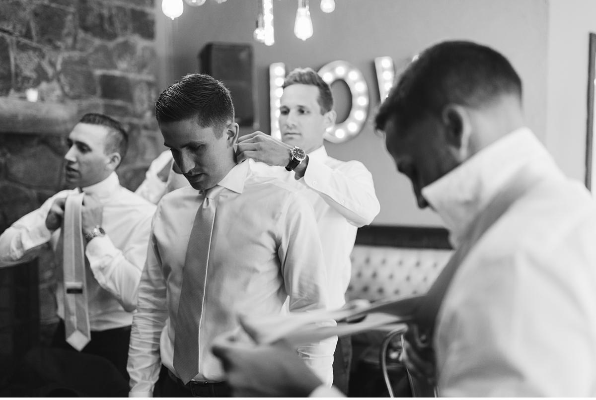 Groomsmen adjusting ties in black and white