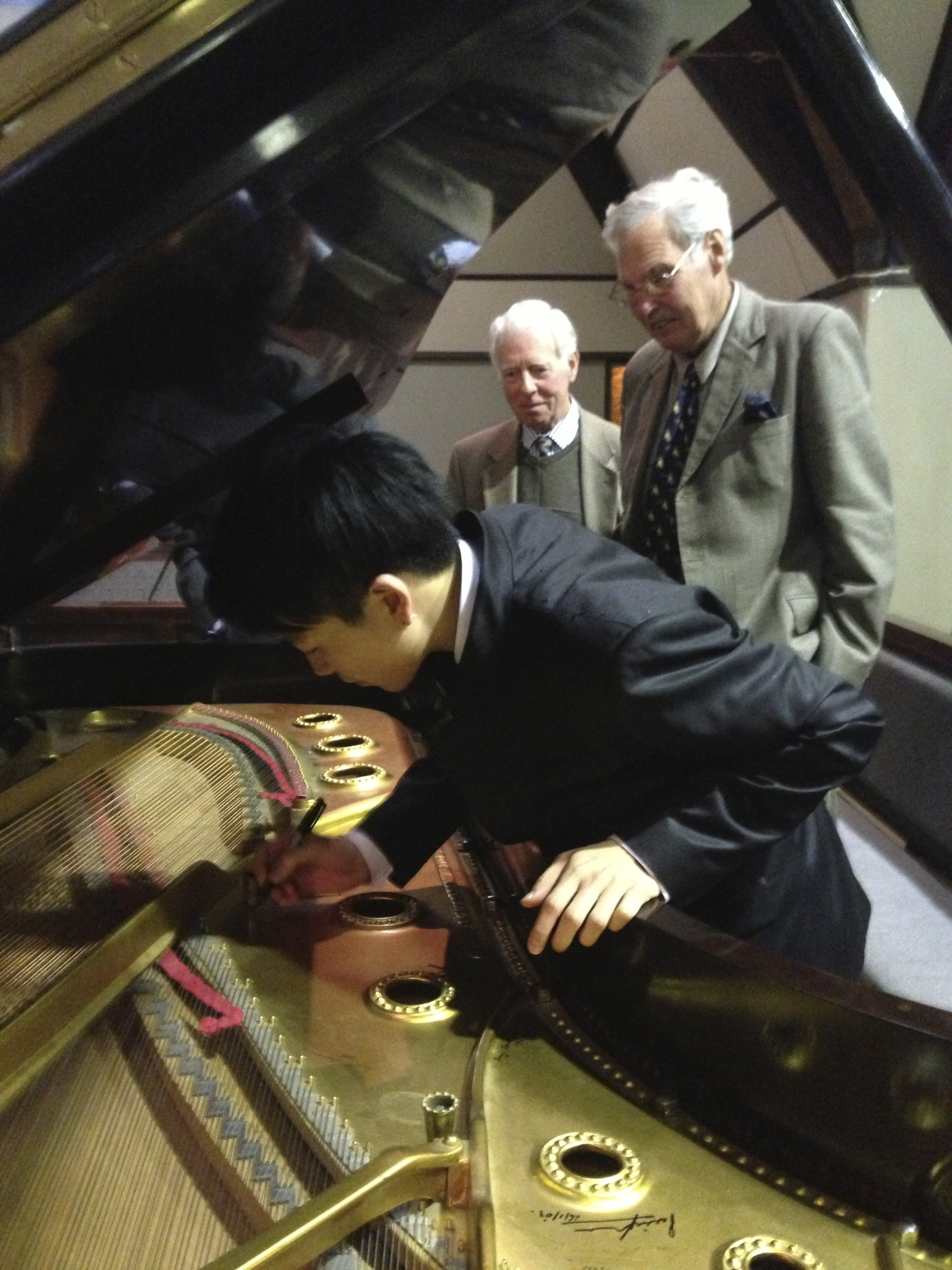 Young pianist Jason Bae signs the Marlborough Music Society's Steinway grand piano, watched by society members Malcolm Tomes, back left, and Alistair Elliott.