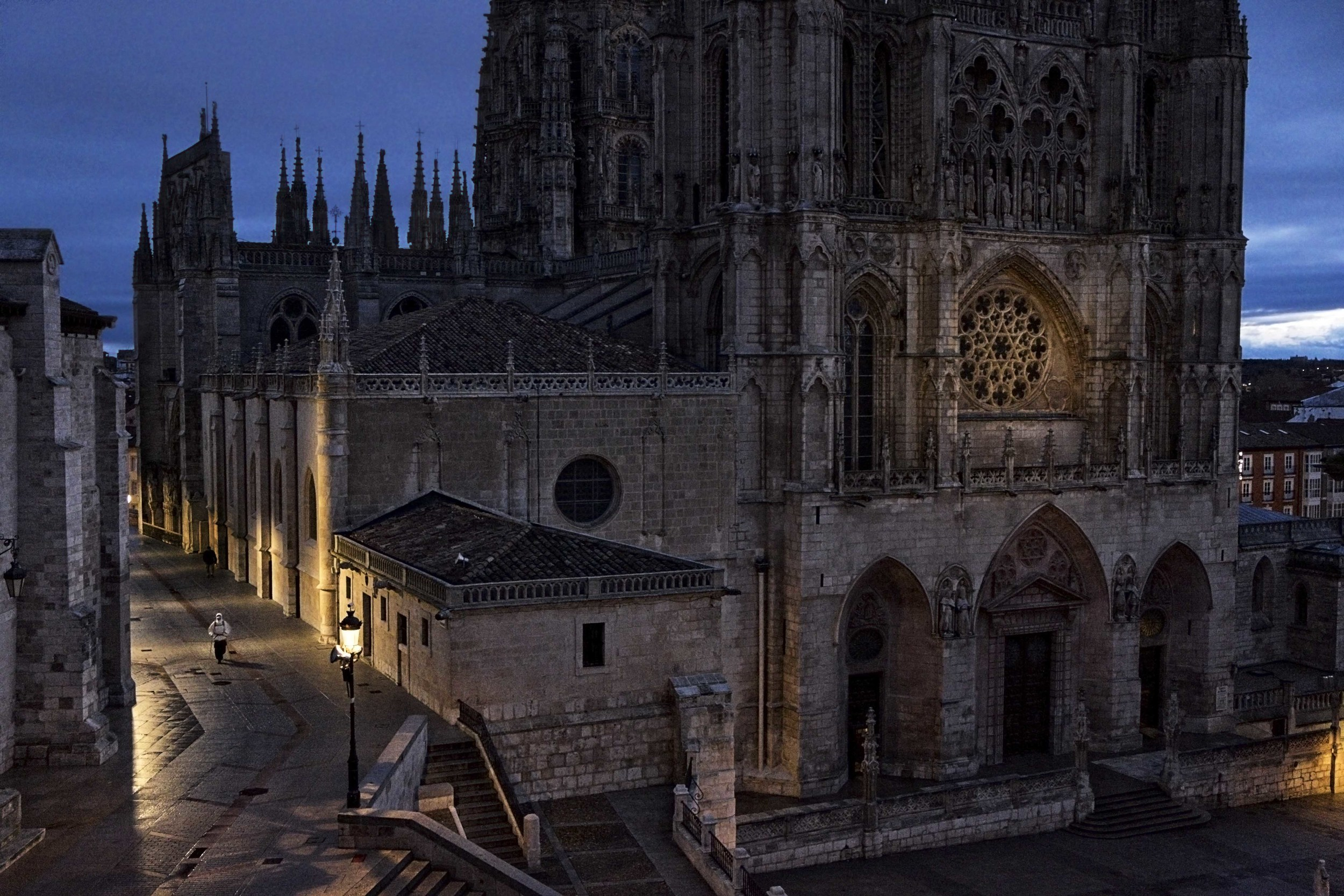 Solitary figure of a pilgrim leaving the city of Burgos early morning beside the 13th century Burgos Cathedral.