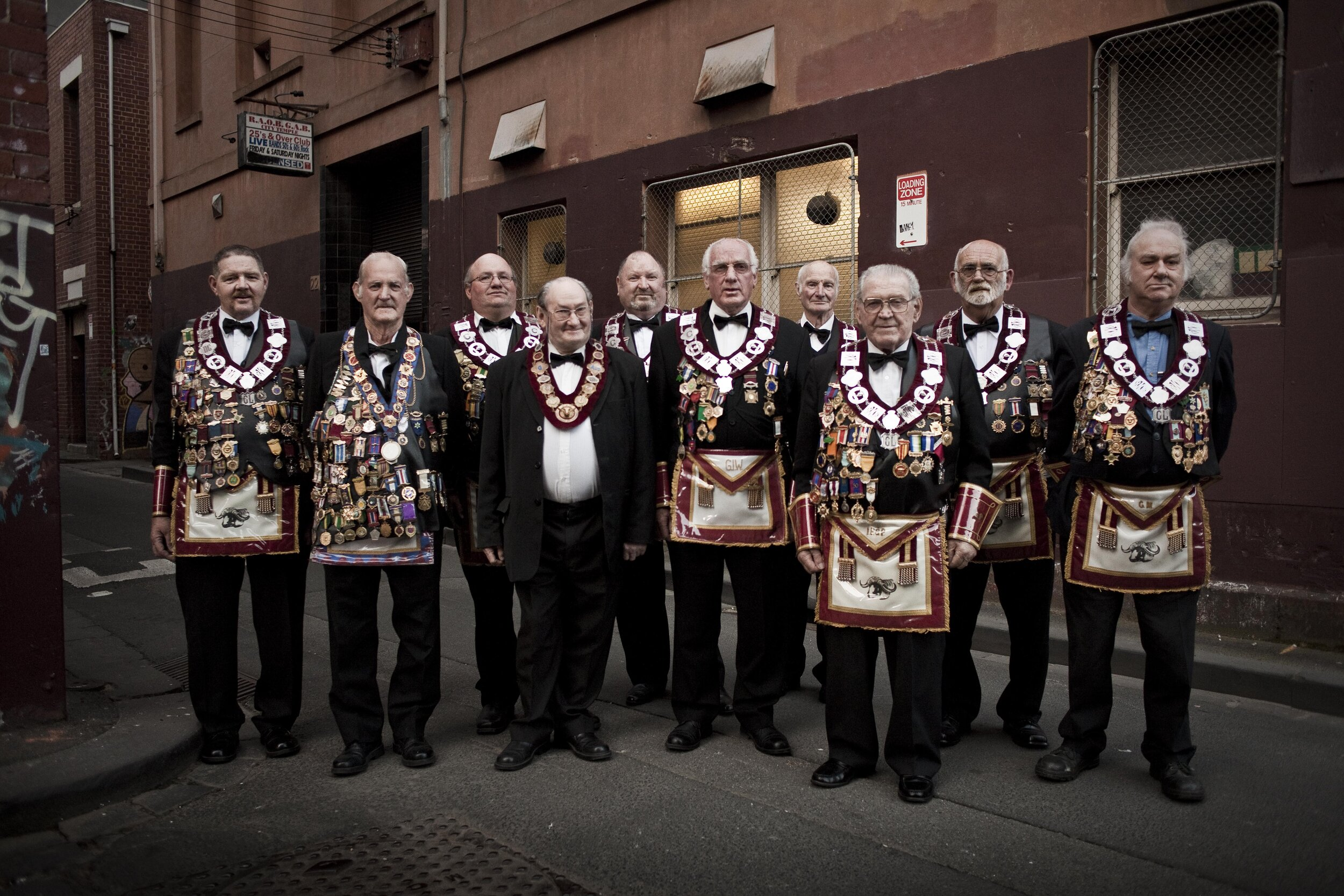"In the late 1950s there were more than 12,000 members at 340 lodges. There are now 32 lodges of mostly elderly members, it's one of Victoria's oldest social clubs, the Royal Antediluvian Order of Buffaloes, or the Buffaloes for short. I took this group portrait of the brothers as they refer to each other in 2010 in front of their clubhouse opposite Guilford lane which they had occupied since the 1950s, sadly they recently had to sell up and this year have relocated somewhere out in the burbs. I fear the wonderful old building with it's ballroom, bar and club room for secret men's business, beautiful old wood-panelled offices and change rooms will be pulled down and replaced by yet another bland apartment block, although the other side of the lane is heritage protected, unfortunately the club house side isn't. Sometimes they are referred to as the ""poor man's Freemasons"", whose members like to dress in ritual garb, and talk, sing and drink together, support sick brethren and raise money for charity. Good-luck brothers!"