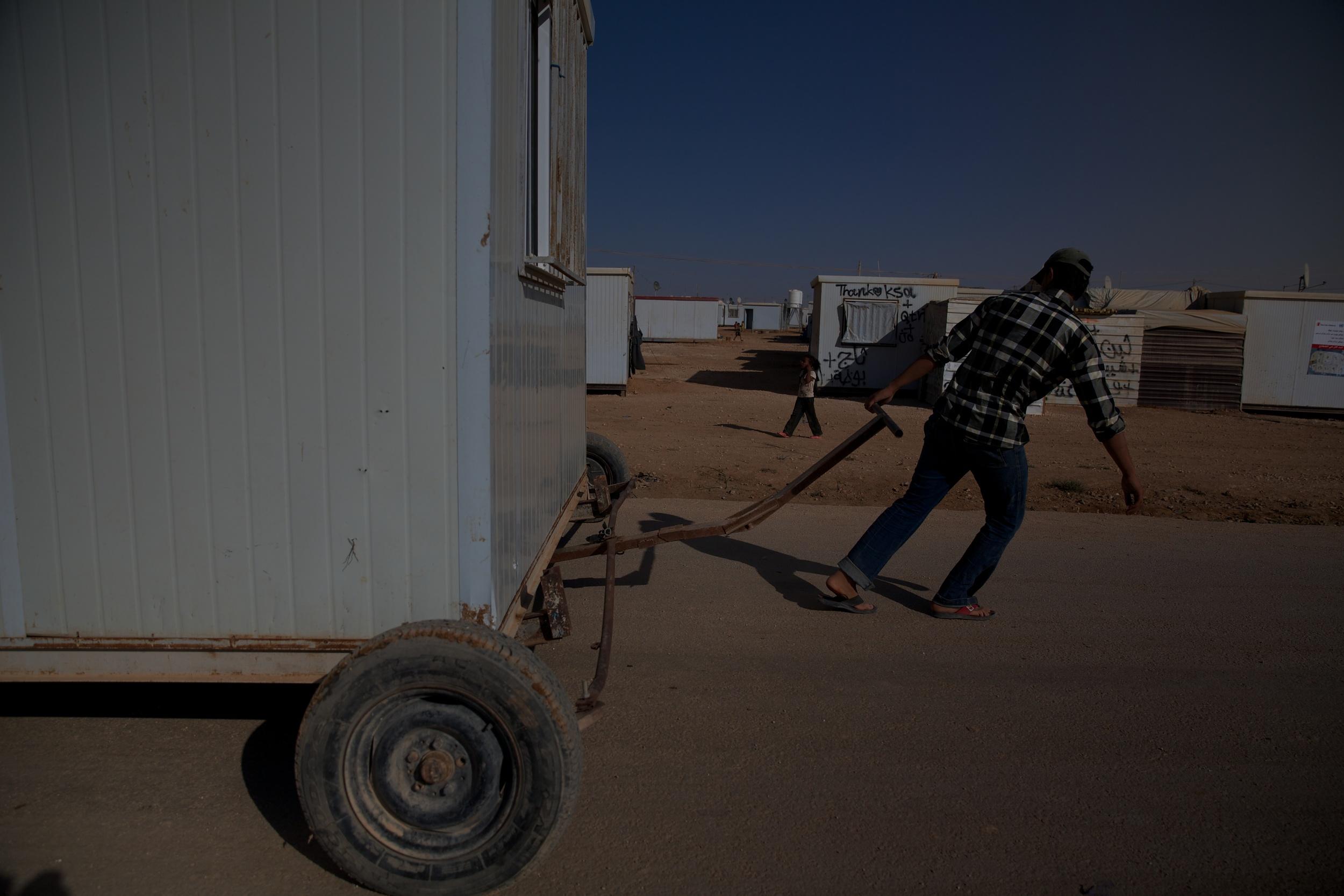 Syrian refugees move a house through the Zaatari refugee camp in Jordan.