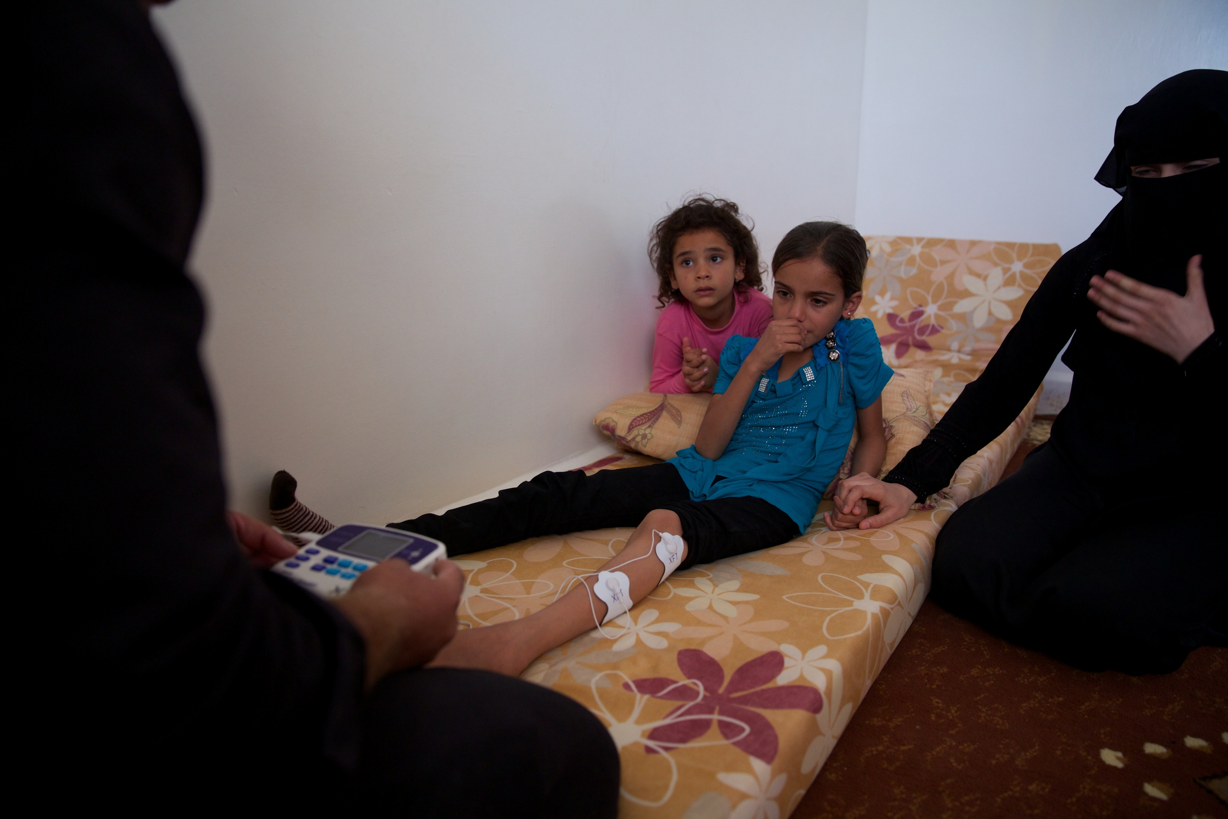 A girl who lost both her parents in the fighting in Syria sees a doctor in Jordan.