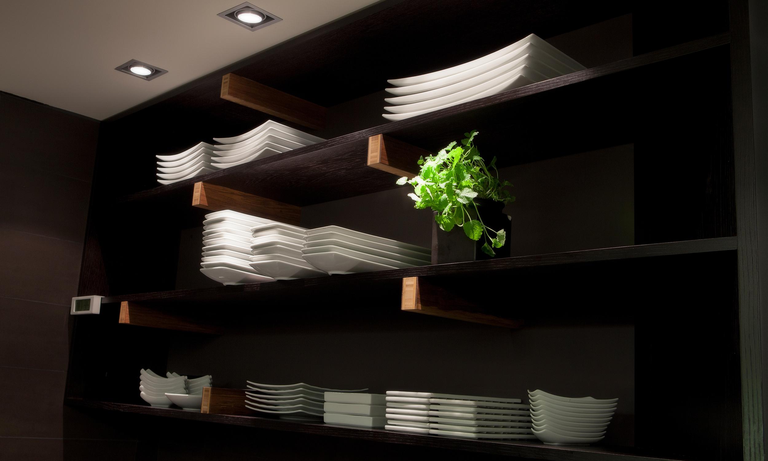 Hyller i kjøkkensonen holdes mørke med detaljer av bambusplater.