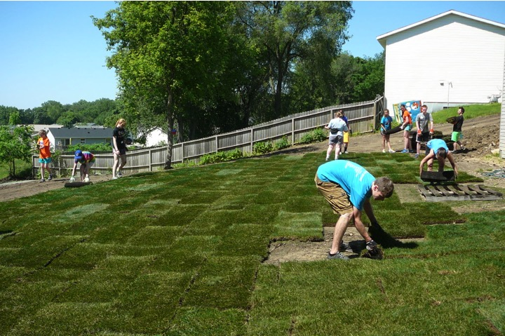 Work crews lay sod at a Habitat for Humanity house.