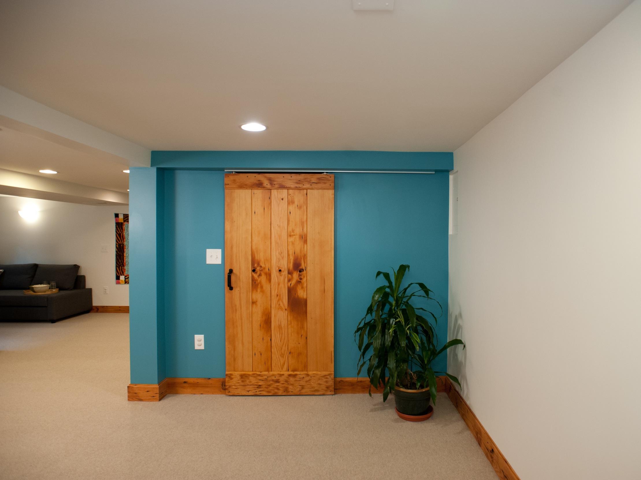 AFTER: Closet gone, custom barn door added, ductwork hidden.
