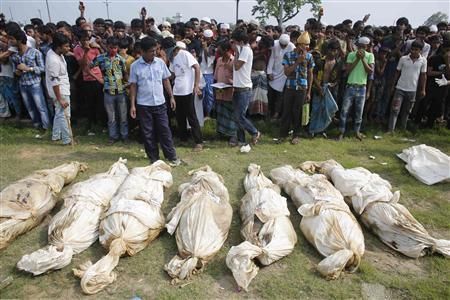 Bodies of unidentified garment workers, who died in the collapse of the Rana Plaza building in Savar, lie on   the ground as people gather to watch a mass burial in Dhaka May 1, 2013  .     Photo Credit: Andrew Biraj for REUTERS