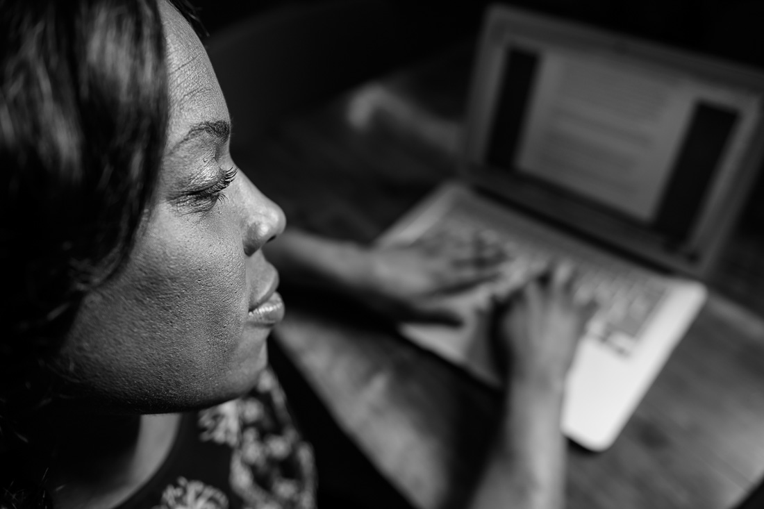 NYC branded lifestyle portrait coach speaker Sandy Rocourt on computer