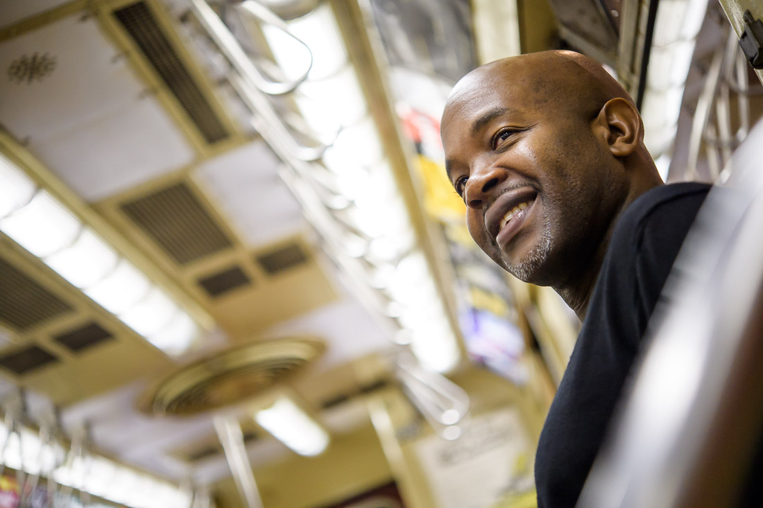 NYC Branded Lifestyle Portrait Podcaster G Moody MTA train smiling while sitting