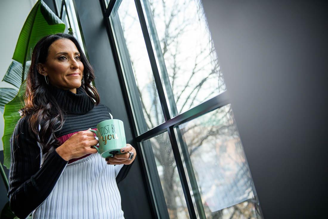 branded lifestyle portrait Kristi Data drinking coffee by window