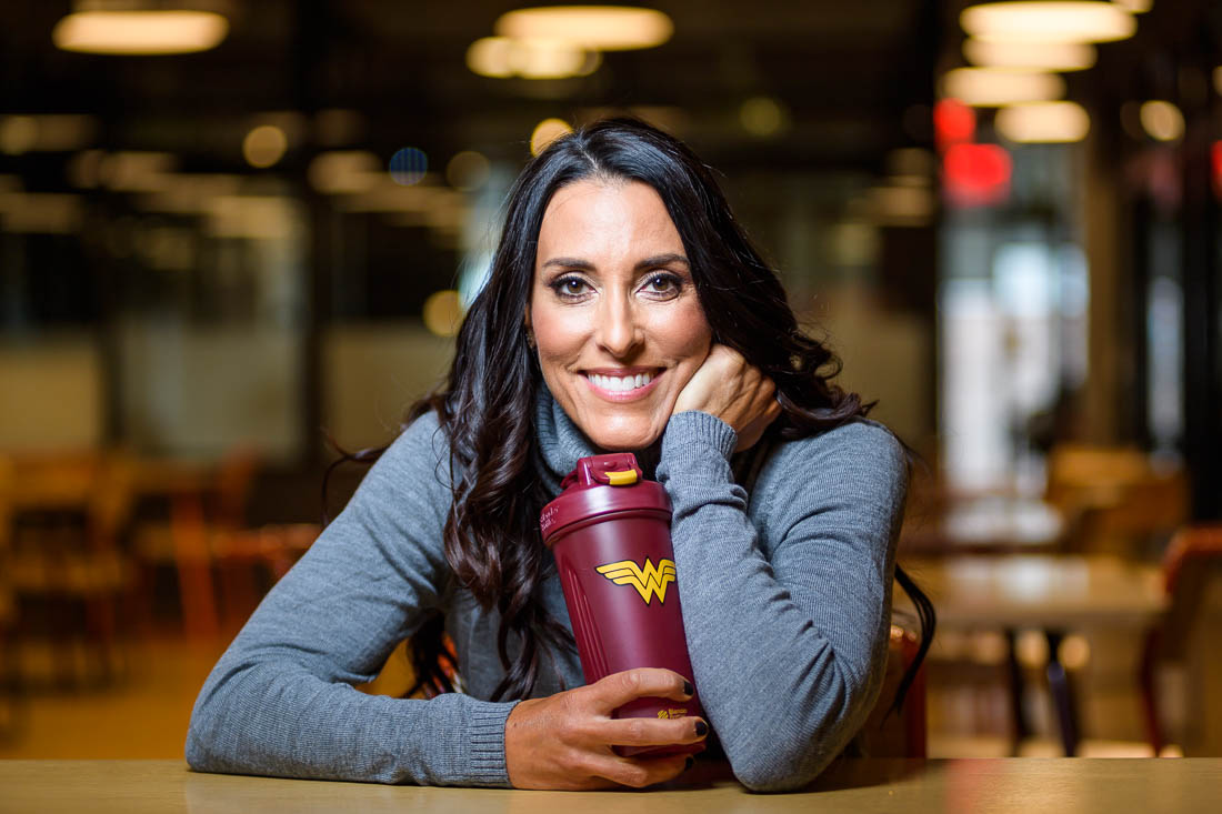 NYC Branded Lifestyle Portrait - coach Kristi Data with superwoman bottle smiling