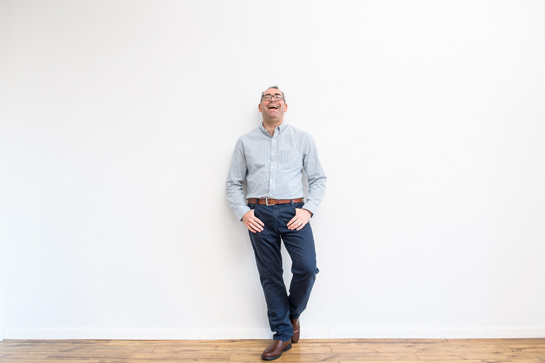 NYC Branded Lifestyle Portrait Mike Roderick leaning on wall laughing