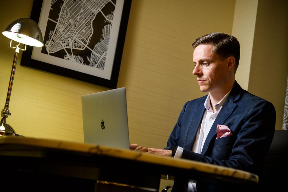 NYC Branded lifestyle portrait keynote speaker James Taylor working on laptop
