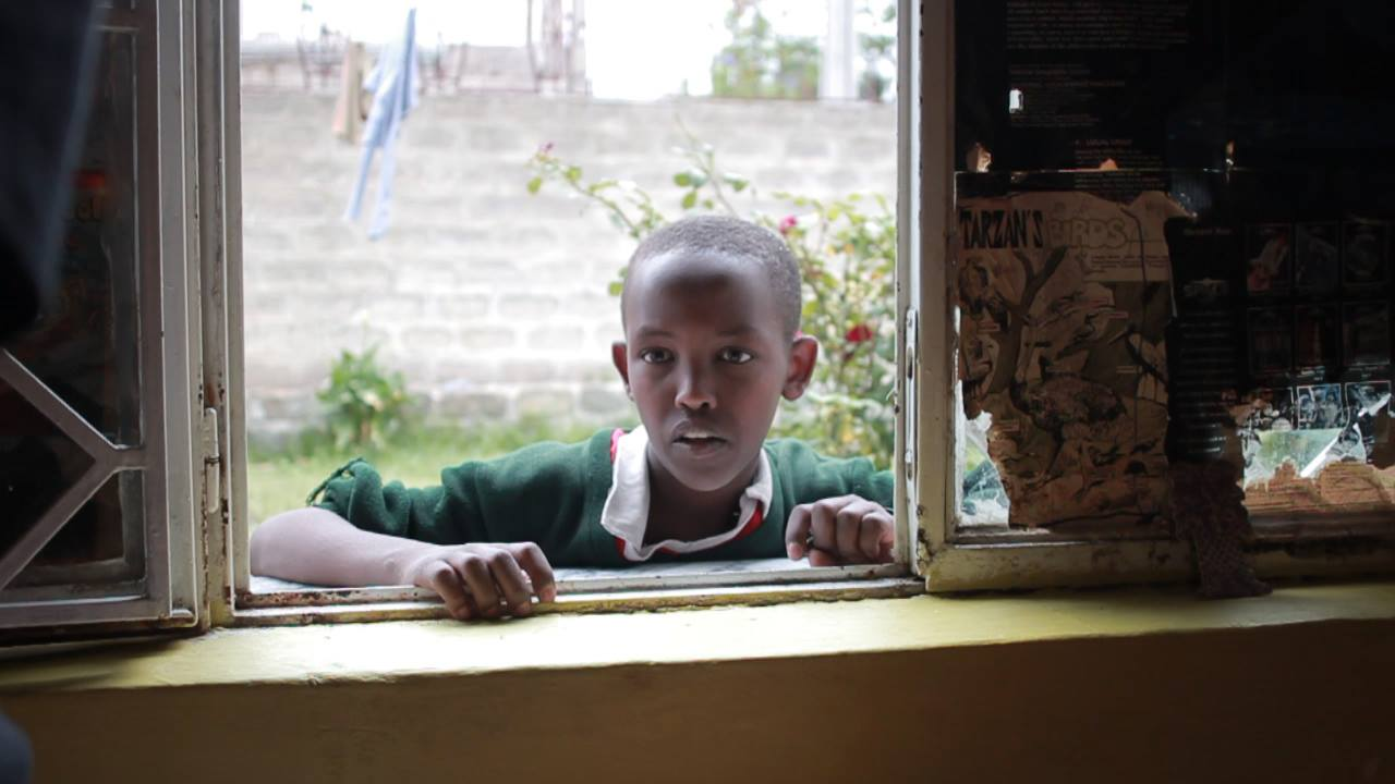 A young boy waits by the window of a library for a book. Part of the educational branch of Youth Impact the library offers free lunches to anyone willing to study hard.  Unicef puts the adult literacy rate of Ethiopia at 39% which is one of the very lowest rates in the world.