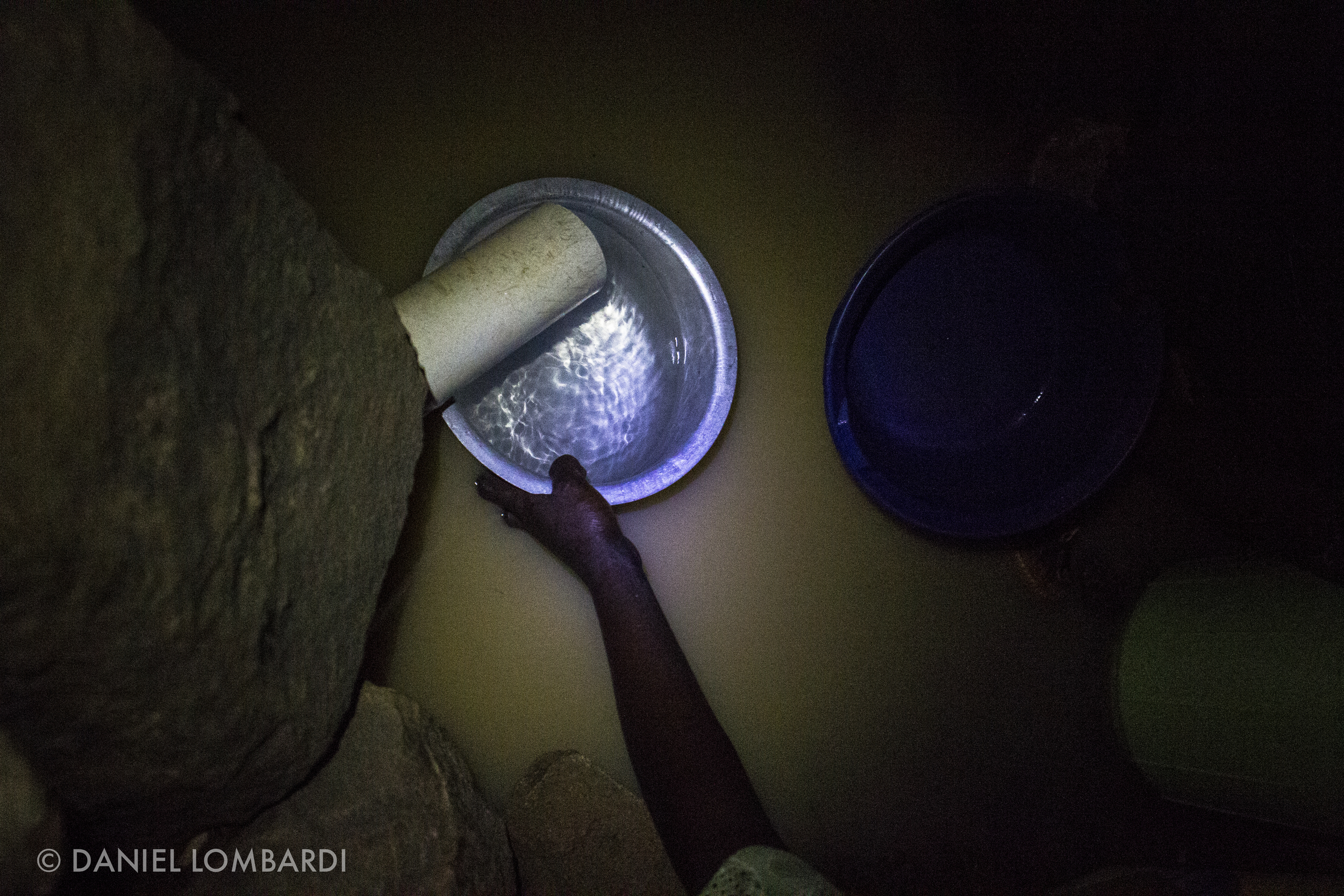 In the dark of night this woman uses a pan to fill her jerrycans scoop by scoop. She finds that the water flows more strongly at night as trees release their grip on the ground water so she can fill her jugs a little faster. However, there is a trade off, at night her fear of violent crime increases.