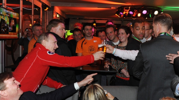 Russian President Vladimir Putin, background left, toasts with beer with people as King Willem-Alexander of the Netherlands, foreground left, and Queen Maxima, foreground centre, look on at the Netherlands house on Feb. 9, 2014 during the Sochi Olympics. (AP Photo/RIA Novosti Kremlin/Mikhail Klimentyev/Presidential Press Service)