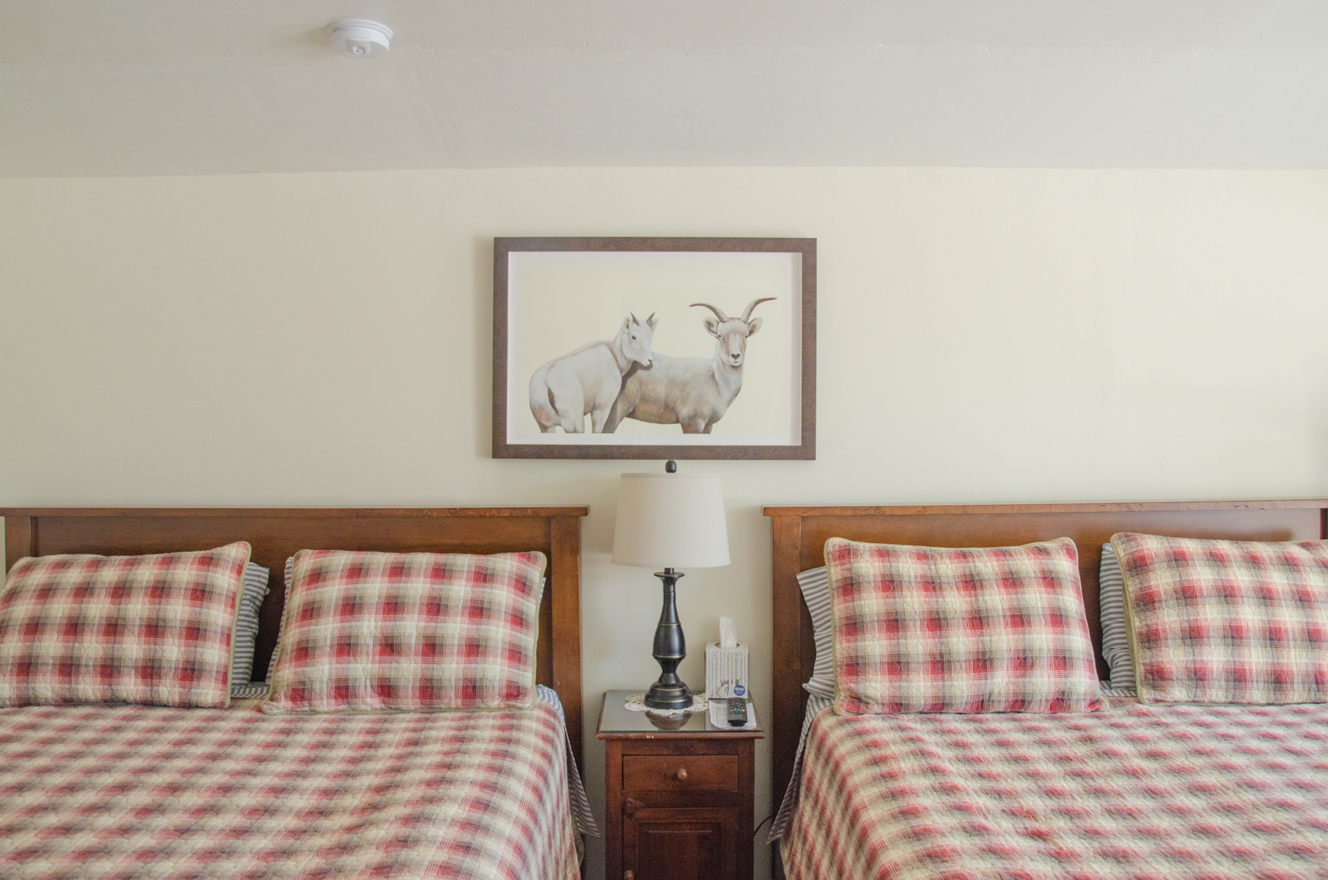 A photo of 2 queen beds in cabin 3 with a painting by artist Jane Kim