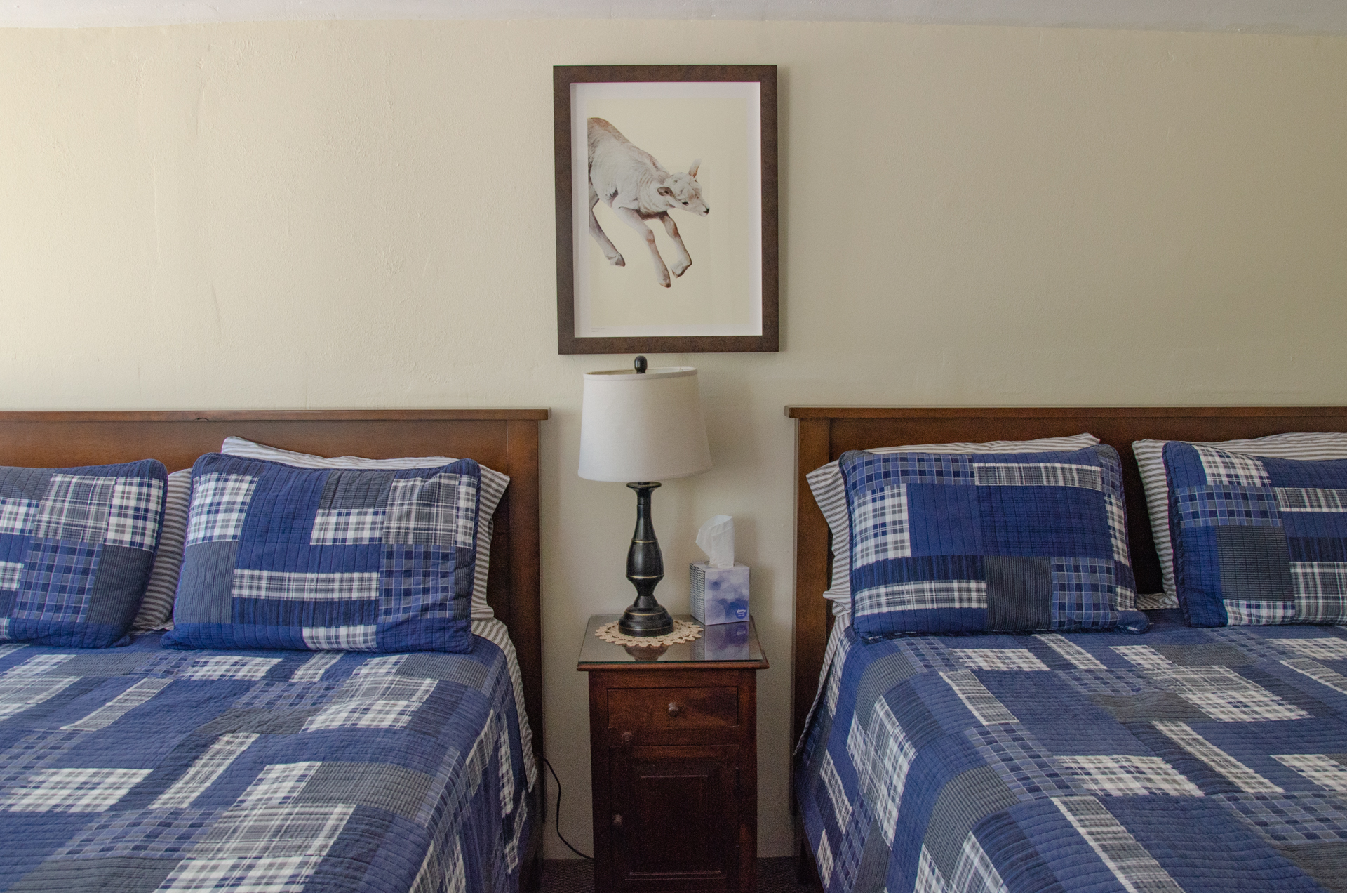 2 queen beds in cabin 3 with painting by Jane Kim