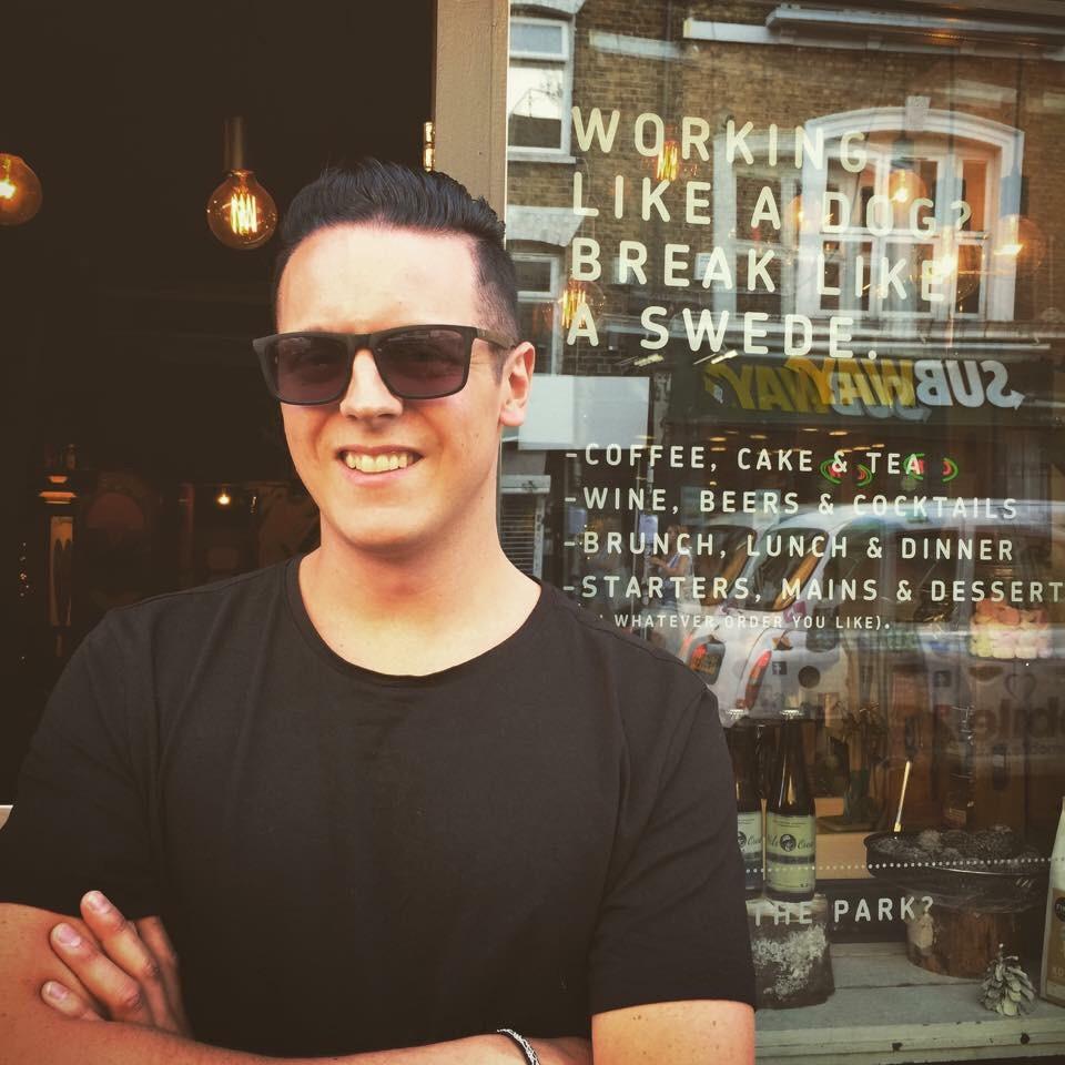 "Fredrik happy to find the ""Working like a dog? Break like a Swede"" coffee shop"