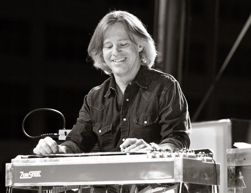 Jim Ashton (Pedal Steel, Guitar, Banjo) On a live music stage most weekends sits a man behind a mechanical marvel of wood, levers, rods, pedals and strings. Gliding a steel bar with one hand and plucking the strings with the other he cajoles a most unique sound, almost effortlessly it seems, in time with the other musicians. The man at the helm of this fantastic instrument, the pedal steel guitar, is North Carolina musician Jim Ashton.