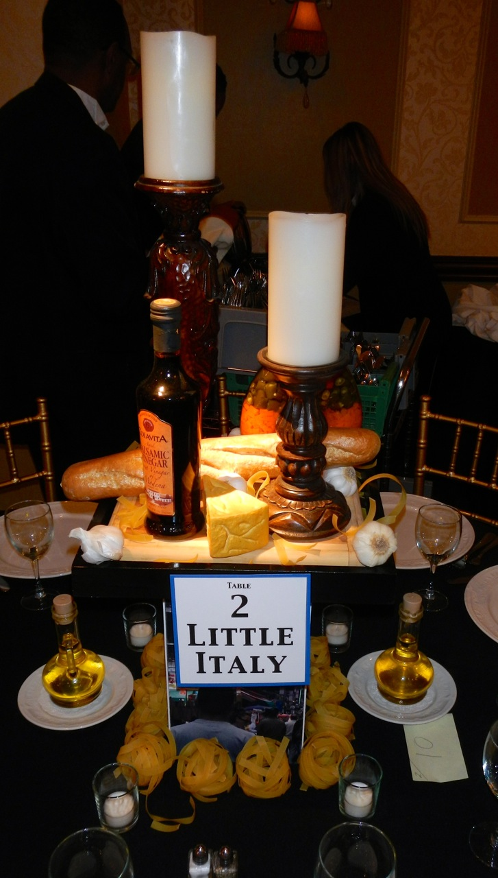 For our Little Italy centerpiece, we featured carved wood candle holders, an assortment of preserved and prop foods, fresh pasta, and images of Little Italy. We even included Egil's favorite: lots of fresh garlic.
