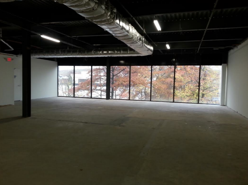 Before: Unappealing lighting, a large window wall with an undesirable view, a concrete floor, and an unfinished ceiling.