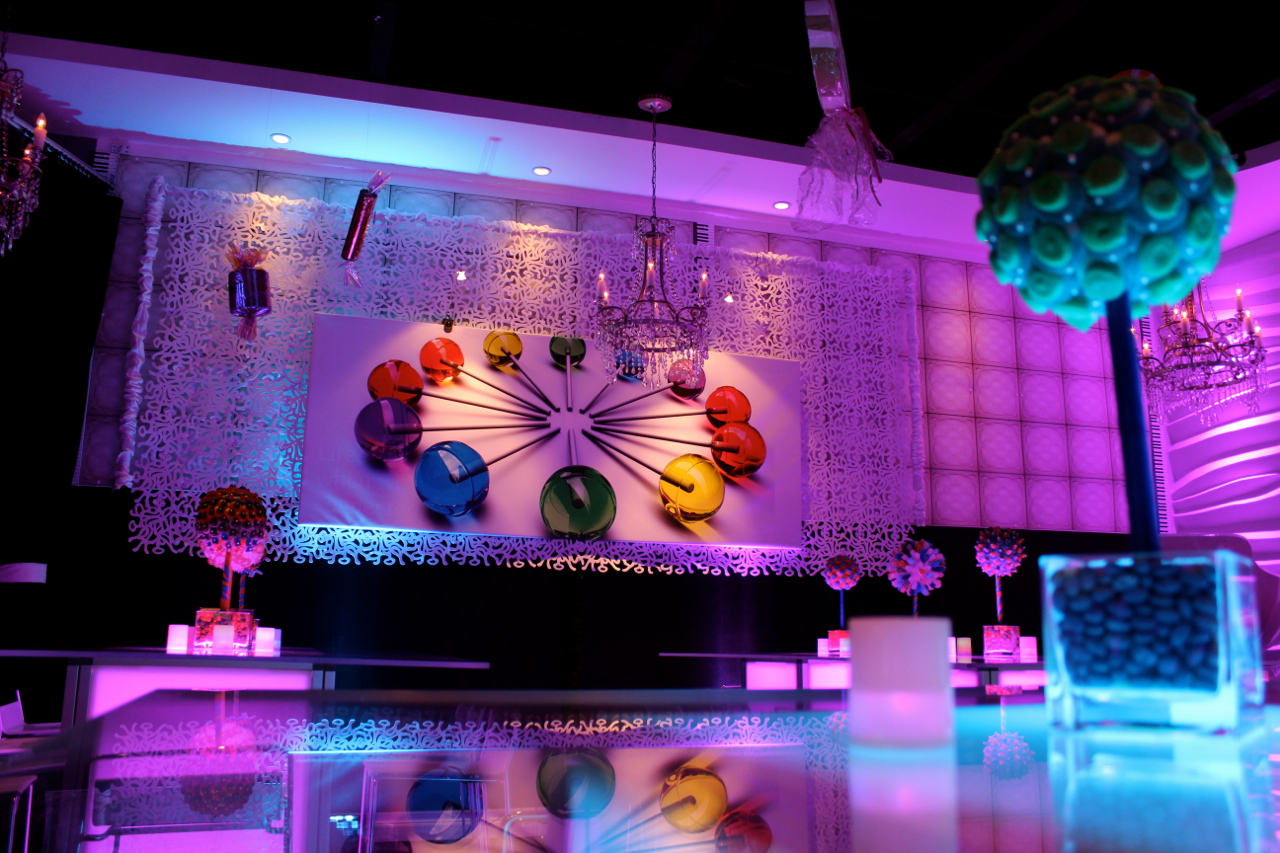 Custom artwork, patterned panel wall art, and glowing acrylic furniture created a chic, modern candy themed display at Vegas NJ in Randolph, New Jersey