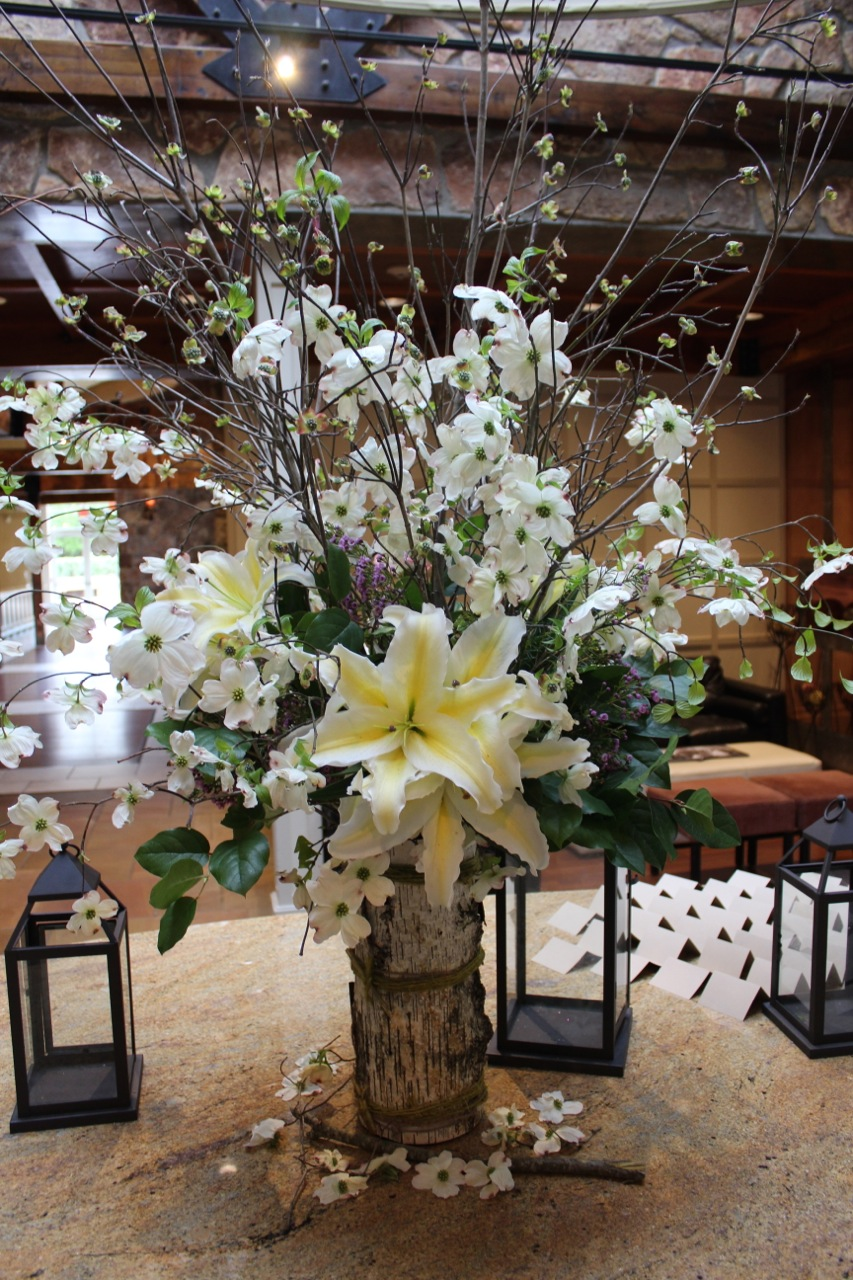 The escort/entry table featured a floral arrangement with giant lilies, live dogwood, and birch.