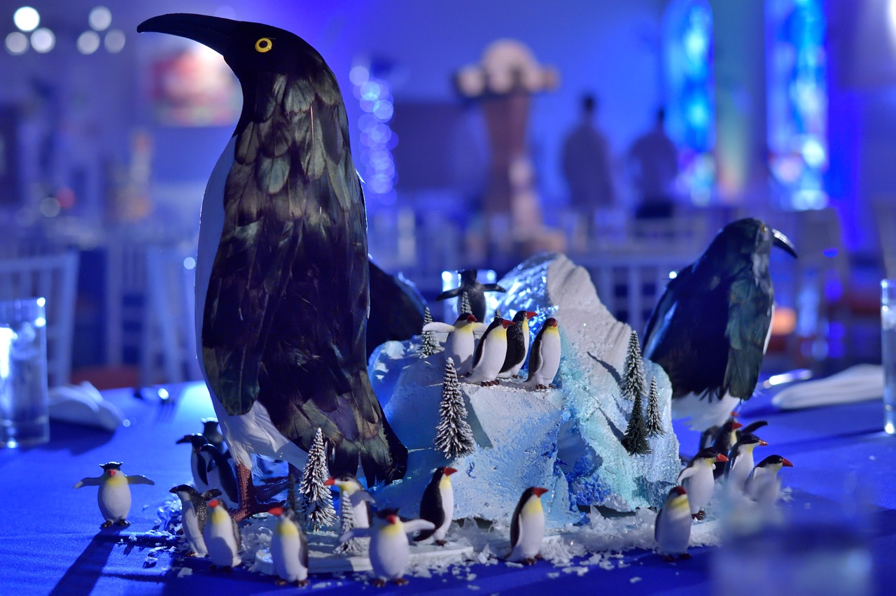 Large penguins and tiny penguins on a snowy mountain created a fun centerpiece that guests can touch and play with